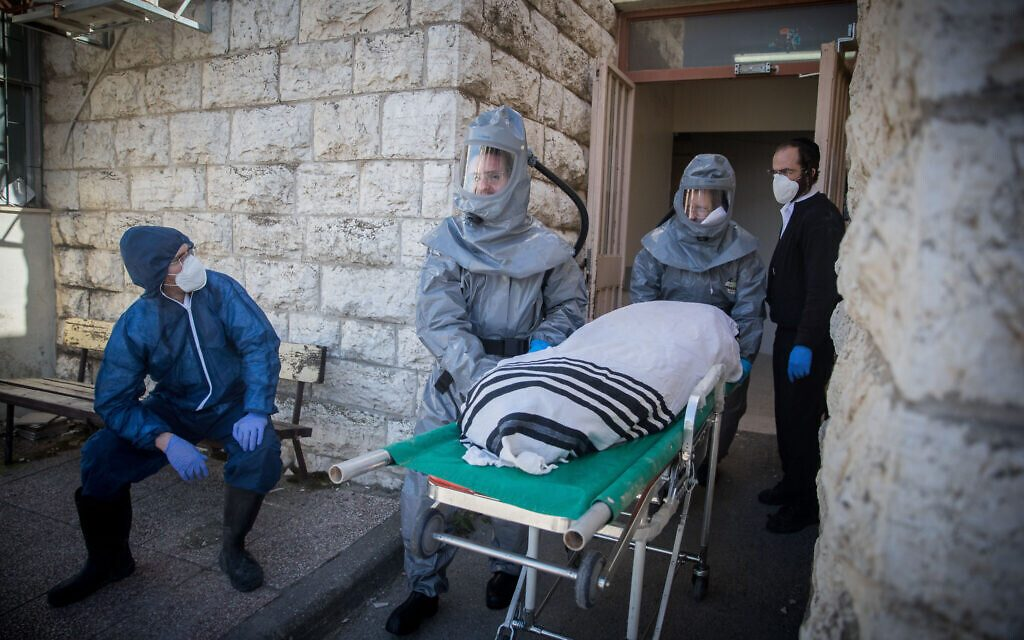 Chevra Kadisha workers wearing protective clothes, carry the body of a patient died from complications of Coronavirus (COVID-19) infection, at the Shamgar Funeral Home in Jerusalem on March 29, 2020. Photo by Yonatan Sindel/Flash90 *** Local Caption *** קורונה וירוס חברה קדישא ירושלים לבושים בגדים מגן נגד